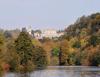 A Stately Home on the River Thames. The River Thames in Autumn with a Stately Home amidst the trees stock photography