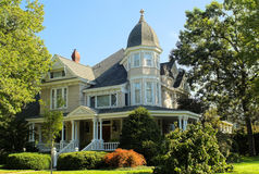 Stately 1940-ish Executive House. Framed by vibrantly green trees, commanding attention through its towering three-story belvedere and wrap-around covered porch royalty free stock photo
