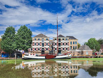Stately monumental mansion with moored boat mirrored in a canal, Gouda, Netherlands. Stately monumental mansion with a white moored boat mirrored in a canal Stock Photo