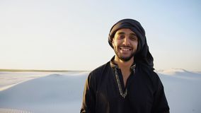 Happy Emirate man walks on outskirts of desert with smile on fac. Stately young Arabian walks and examines expanses of wide sandy desert. male tourist smiles and royalty free stock images