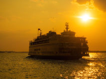 The Staten Island Ferry sailing on the New York Harbor at sunset Stock Photo