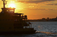 Staten Island Ferry into the Sun. The Dark Silhouette of Staten Island Ferry against the Sun at Sunset Royalty Free Stock Images