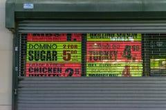 Staten Island NY/USA - 06/22/2018: Annonseringar bak de stängda portarna av en supermarket royaltyfri fotografi