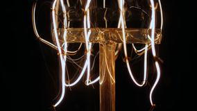 Switch on modern retro led light close up slow motion. Static close up super slow motion shot of the wires within a vintage look modern LED carbon filament lamp stock video
