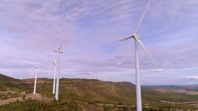Wind turbine farm on mountain landscape at sunset