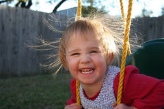 Static Electricity in the Air. A little girl laughs at the effects of static electricity on her hair while she swings Stock Images