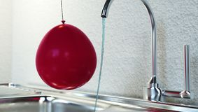 Static electricity experiment with balloon and tap water. The electrified balloon draws water from the faucet Stock Images