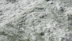 Static medium high angle shot of swirling water waves coming from the irrigation dam spillway. Alfonso Lista, Ifugao, Philippines - July 18, 2017:  Static medium stock video