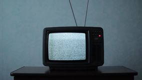 Retro TV with white noise in a dark room. Static noise on a vintage TV set in a dark room stock footage