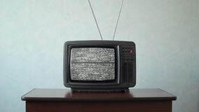 No signal just noise on old analogue TV set. Static noise on a vintage TV set in a room stock video footage