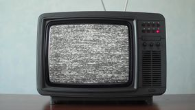 Static noise on a vintage TV set in a room. No signal just noise on a small TV in a room stock video
