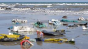 Static shot of sea. close up of plastic garbage and trash on beach in defocus. Static shot of dirty sea. close up of plastic garbage and trash on beach in stock footage
