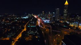 Static shot of the lit up nighttime Atlanta Skyline with traffic below. Freway headlights. Downtown view. Camera stock video