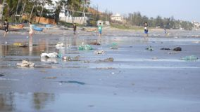 Static shot of playing children in defocus on beach polluted by trash, garbage. Static shot of beach polluted by trash and garbage on playing football children stock video footage