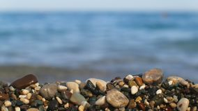 Static shot of seacoast of Turkey, close up of multi color pebble, defocused sea waves in background. 4K stock footage