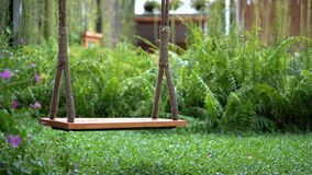 Static Swing without movement in the garden with blurs fern background.