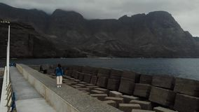 Static view from the drone on a young girl standing on a pier on a dark day. Agaete, Gran Canaria, Spain. 2k stock footage