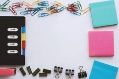 Stationärer Satz des Büros einschließlich Notizbuch, Büroklammer, klebrigen Notizblock, Mappenclip, Heftklammern und Hefter auf w Lizenzfreie Stockfotografie
