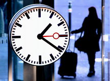 Station clock and a passenger Stock Photos