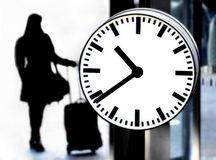 Station clock and a passenger waiting with baggage Royalty Free Stock Images