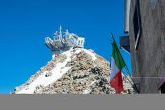 Station de benne suspendue Punta Helbronner dans le ciel bleu avec le drapeau italien photos stock