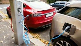 Station de charge sur une rue de ville Un câble est relié à la station, qui charge deux voitures électriques banque de vidéos