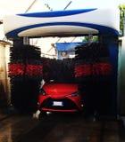 Station de lavage automatique dans l'action, procédé de lavage sur une voiture rouge image stock