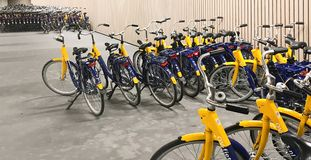 Station de location de bicyclette jaune sur la rue de ville photo libre de droits