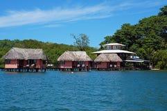 Station de vacances d'Eco avec le pavillon couvert de chaume au-dessus de l'eau Images stock