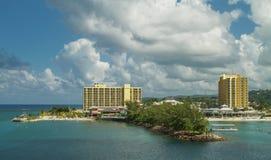 Station de vacances d'hôtel avec la plage entourée par l'océan et le ciel avec des nuages Images stock
