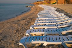 Station de vacances de mer avec les canapés blancs vides du soleil Lever de soleil sur la plage photographie stock libre de droits