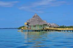 Station de vacances tropicale avec les pavillons couverts de chaume au-dessus de l'eau Photographie stock
