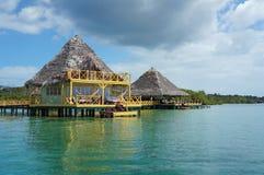 Station de vacances tropicale d'eco au-dessus de l'eau avec le toit couvert de chaume Photo stock
