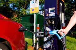 Station för UK-elbiluppladdning med bilen som laddas Arkivfoton