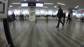 Station of luchthavenzaal, mensen die kaartjes kopen bij bespreekbureauvensters stock videobeelden