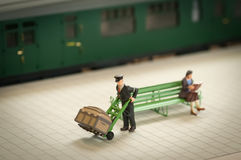 Station porter. Miniature figure of a railway station porter moving luggage - shallow d.o.f Stock Photo