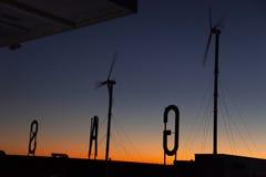 Station service avec des moulins à vent dans le coucher du soleil Photographie stock libre de droits