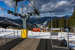 Station of ski lift with chairs against mountain view in a ski-r. Esort on a sunny day in winter period Stock Photos