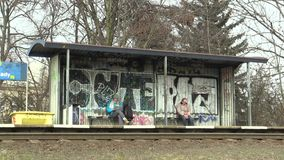 OLOMOUC, CZECH REPUBLIC, MARCH 29, 2018: The station stops on a graffiti railway station sprayed and two waiting people. The station stops on a graffiti railway stock footage