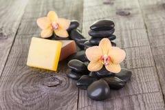 Station thermale avec des fleurs, des savons et des pierres noires Photographie stock