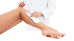 Station thermale de beauté Procédure de cosmétologie d'épilation Esthéticien cirant les jambes femelles photos libres de droits