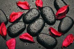Station thermale de fond. pierres noires et pétales rouges Photos stock
