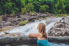 Station thermale géothermique Femme détendant dans la piscine de source thermale dans la perspective d'une cascade Photo libre de droits