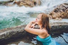 Station thermale géothermique Femme détendant dans la piscine de source thermale dans la perspective d'une cascade Photos libres de droits