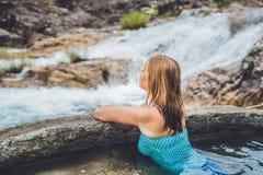 Station thermale géothermique Femme détendant dans la piscine de source thermale dans la perspective d'une cascade Photographie stock libre de droits