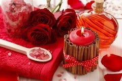 Station thermale réglée : bougie parfumée, sel de mer, savon liquide et rouge romantique images libres de droits
