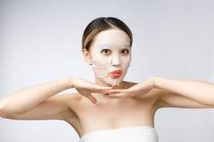Station thermale, soins de santé Fille asiatique avec un isolat cosmétique de masque sur le blanc photographie stock