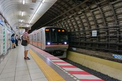 Station of Tokyo metro with approaching train and people on plat. Tokyo, Japan - August 29, 2016: Subway underground station of Tokyo metro with approaching Stock Photo