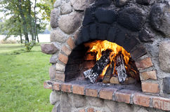 Stationary barbecue. Fireplace with burning wood at summer day Royalty Free Stock Photography