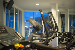 Stationary bicycle standing in a fitness gym at evening Stock Photo
